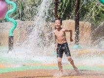 Petit garçon d'enfant asiatique ayant l'amusement à jouer avec de l'eau dans le fou de parc Photographie stock