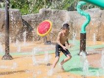 Petit garçon d'enfant asiatique ayant l'amusement à jouer avec de l'eau dans le fou de parc Photographie stock libre de droits