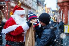 Petit garçon d'enfant en bas âge avec le père et la Santa Claus sur le marché de Noël Photographie stock