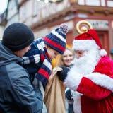 Petit garçon d'enfant en bas âge avec le père et la Santa Claus sur le marché de Noël Photo stock
