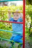 Petit garçon d'enfant en bas âge ayant l'amusement à un terrain de jeu Images stock