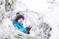 Petit garçon d'enfant en bas âge ayant l'amusement avec la neige dehors sur de beaux WI Image libre de droits