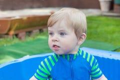Petit garçon d'enfant en bas âge ayant la petite piscine d'amusement en été Photographie stock