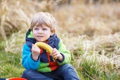 Petit garçon d'enfant en bas âge ayant le pique-nique près du lac de forêt, nature Photos stock