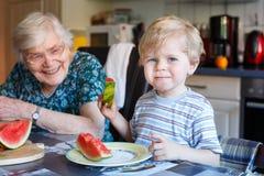 Petit garçon d'enfant en bas âge et son arrière grand-mère mangeant la pastèque a Images stock