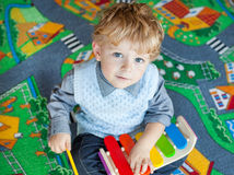 Petit garçon d'enfant en bas âge jouant avec le jouet en bois de musique Images stock