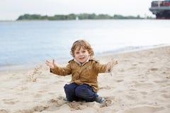 Petit garçon d'enfant en bas âge jouant avec le sable sur la plage de la rivière Elbe Photo libre de droits