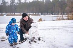 Petit garçon d'enfants de mêmes parents faisant un bonhomme de neige avec le grand-père, jouant et ayant la neige d'amusement, de Photo libre de droits