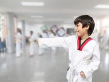 Petit garçon dans des activités d'intérieur de classe du Taekwondo Images libres de droits