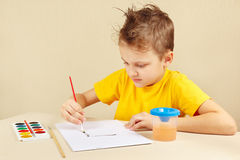 Petit garçon dans des couleurs jaunes de peinture de chemise Images stock