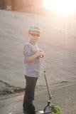 Petit garçon dans des lunettes de soleil et un chapeau montant un scooter, Image libre de droits