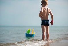 Petit garçon dans des lunettes de soleil jouant avec le bateau de jouet images stock