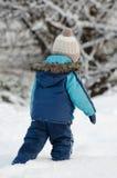 Petit garçon dans l'habillement d'hiver marchant dans la neige, vue du dos Photos stock