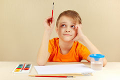 Petit garçon dans la chemise orange allant peindre des couleurs Photo libre de droits