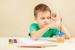 Petit garçon dans la chemise verte allant peindre des couleurs Photo libre de droits