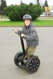 Petit garçon dans la conduite de casque sur segway Photos stock