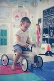Petit garçon dans la cour de jeu Voiture d'enfants de dessin de petit garçon Photographie stock libre de droits
