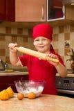 Petit garçon dans la cuisine avec le secteur de traitement au four Image libre de droits