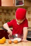 Petit garçon dans la cuisine avec le traitement au four Image stock