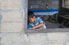 Petit garçon dans la fenêtre. Vang Vieng. Les Laotiens. Photo stock