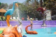 Petit garçon dans la piscine avec l'éclaboussement de fontaines Photographie stock libre de droits