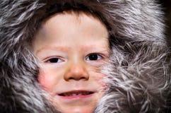 Petit garçon dans le capuchon de fourrure photographie stock