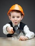 Petit garçon dans le casque avec le modèle et la règle de maison photo stock
