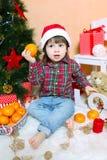 Petit garçon dans le chapeau de Santa avec la mandarine Image libre de droits
