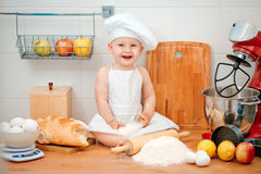 Petit garçon dans le costume de cuisinier à la cuisine avec du pain Image stock
