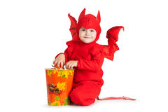 Petit garçon dans le costume de diable rouge se reposant près du grand seau Photographie stock