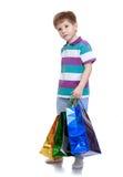Petit garçon dans le T-shirt rayé tenant des sacs pour Images libres de droits