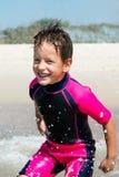 Petit garçon dans son costume de plongée souriant à la plage image stock