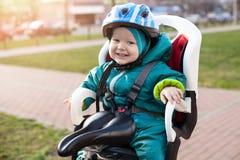 Petit garçon dans un siège de vélo Photo stock