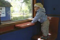 Petit garçon dans un train de voyageurs Photos stock