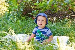 Petit garçon dans une chemise rayée, un chapeau bleu et un sourire Photographie stock