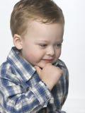 Petit garçon dans une pose pensante. photo stock