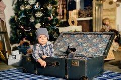 Petit garçon dans une valise dans le décor de Noël, l'enfant par nouvelle année Photos libres de droits