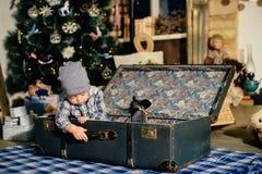 Petit garçon dans une valise dans le décor de Noël, l'enfant par nouvelle année Photos stock