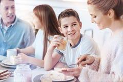 Petit garçon de sourire appréciant le jus d'orange pendant le petit déjeuner de famille Photo stock