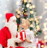Petit garçon de sourire avec le père noël et des cadeaux Photo libre de droits