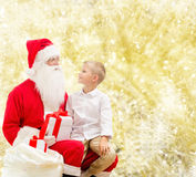 Petit garçon de sourire avec le père noël et des cadeaux Images libres de droits
