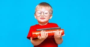 Petit garçon de sourire en verres ronds tenant une pile de livres ?ducation Pr?parez ? l'?cole photos stock