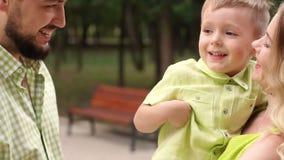 Petit garçon de sourire heureux dans les mains d'une maman et d'un papa affectueux en parc banque de vidéos