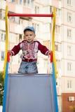 Petit garçon de sourire heureux sur le terrain de jeu Photographie stock libre de droits