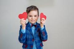 Petit garçon de sourire mignon dans le costume tenant les coeurs rouges sur des bâtons photo libre de droits