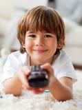 Petit garçon de sourire regardant la TV se trouver sur l'étage Images stock