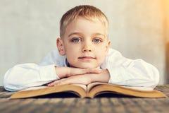 Petit garçon de sourire s'asseyant avec ses mains sur le livre Photos libres de droits