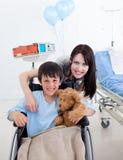 Petit garçon de sourire s'asseyant sur le fauteuil roulant Photos stock