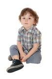 Petit garçon de trois ans s'asseyant sur le plancher Image libre de droits