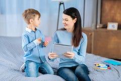 Petit garçon donnant l'autocollant de note à sa maman tenant le carnet Photographie stock libre de droits